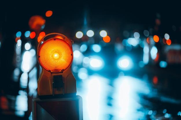 Close de uma lâmpada de advertência na rua à noite