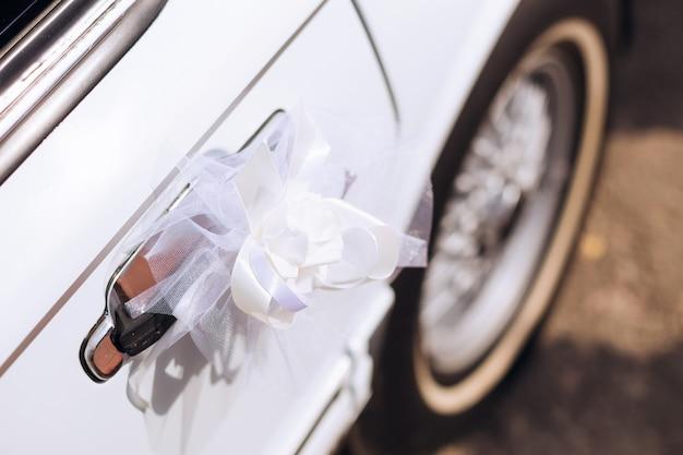 Close de uma limusine branca com maçanetas decoradas um lindo laço branco adorna a maçaneta de um transporte chique