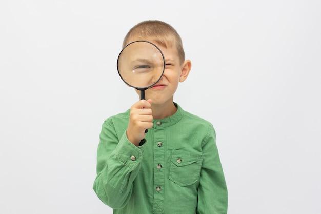 Close de uma linda criança olhando através de uma lente de aumento sobre o branco