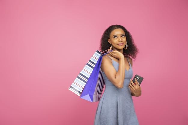 Close de uma linda garota afro-americana segurando sacolas de compras, smartphone e cartão de crédito
