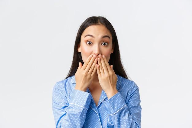 Close de uma linda garota asiática chocada e espantada de pijama azul percebendo algo, segurando as mãos na boca e olhos esbugalhados maravilhados com a câmera, ouvir fofocas, fundo branco