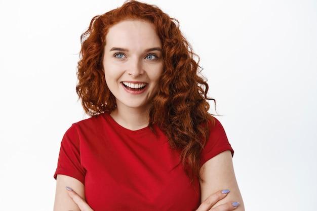 Close de uma linda garota boba com cabelo ruivo cacheado, sorrindo, satisfeita e determinada a comprar alguma coisa, braços cruzados no peito, parede branca