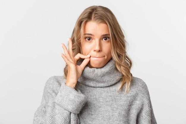 Close de uma linda garota loira com um suéter cinza, mantendo sua promessa, fechando os lábios, guardando segredo
