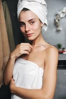 Close de uma linda jovem com uma toalha enrolada na cabeça e tocando sua pele com uma pena no banheiro