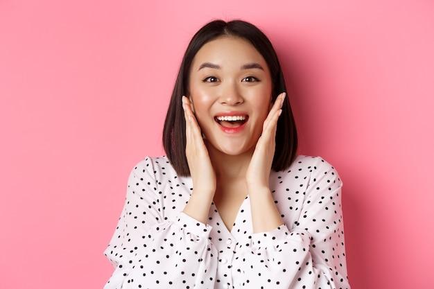 Close de uma linda mulher asiática tocando o rosto de pele limpa e olhando para a câmera maravilhada, em pé sobre a rosa