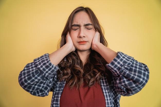 Close de uma linda mulher cobrindo as orelhas com as duas mãos e fechando os olhos