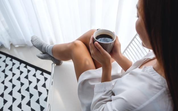 Close de uma linda mulher tomando café quente no quarto em casa de manhã