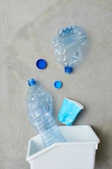 Close de uma lixeira ecológica com garrafas de plástico selecionadas