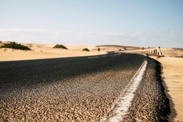 Close de uma longa estrada com dunas de areia do deserto nas laterais