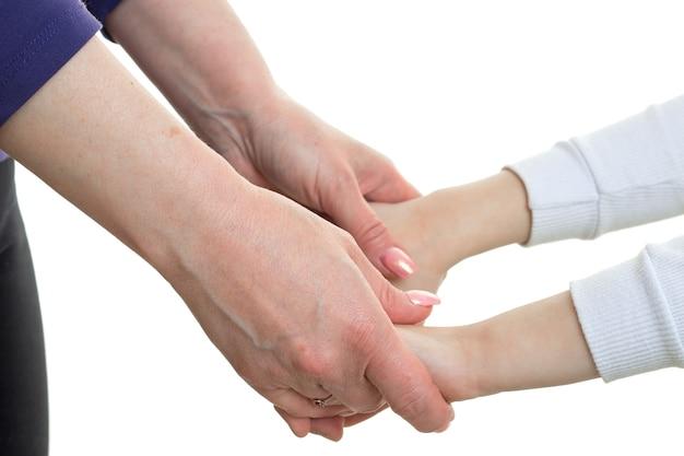 Close de uma mãe segurando a filha pela mão