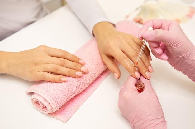 Close de uma manicure aplicando óleo hidratante para unhas na mão de uma pessoa