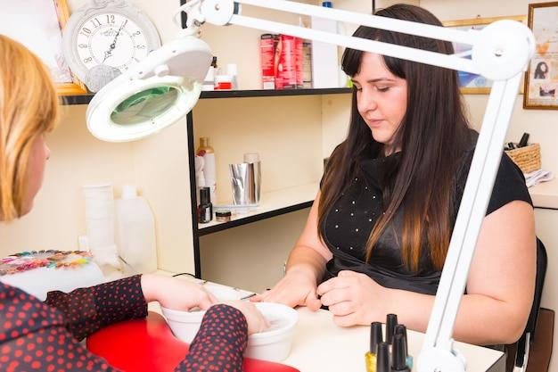 Close de uma manicure morena preparando ferramentas enquanto uma mulher loira molha as mãos em pequenas tigelas de água durante o tratamento de manicure no spa