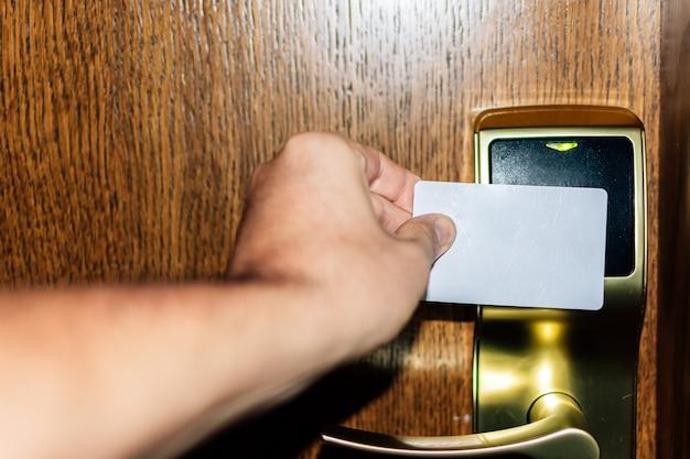 Close de uma mão abrindo a porta de um quarto de hotel com um cartão