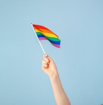 Close de uma mão acenando uma pequena bandeira de arco-íris contra um azul claro