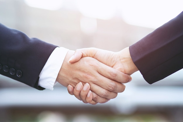 Close de uma mão de empresário apertar a empresária entre dois colegas ok, sucesso nos negócios de mãos dadas.