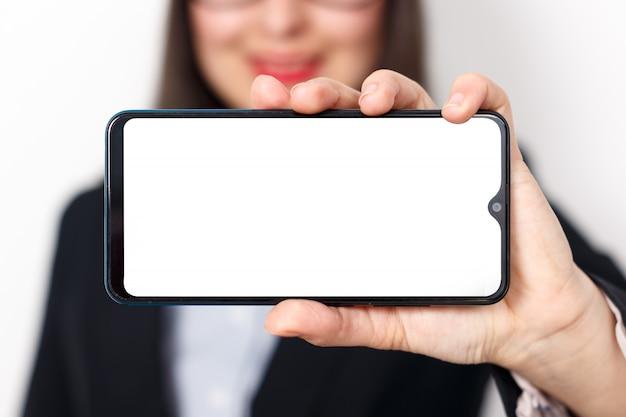 Close de uma mão de mulher mostrando uma tela horizontal em branco smartphone