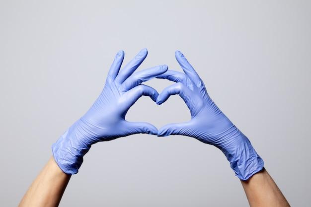Close de uma mão em luvas roxas médicas de borracha de látex dobradas em um sinal de coração