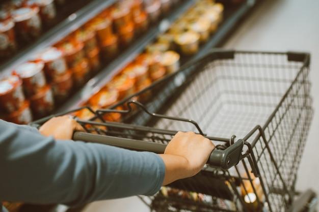 Close de uma mão feminina com carrinho de compras no supermercado. conceito de supermercado de compras.