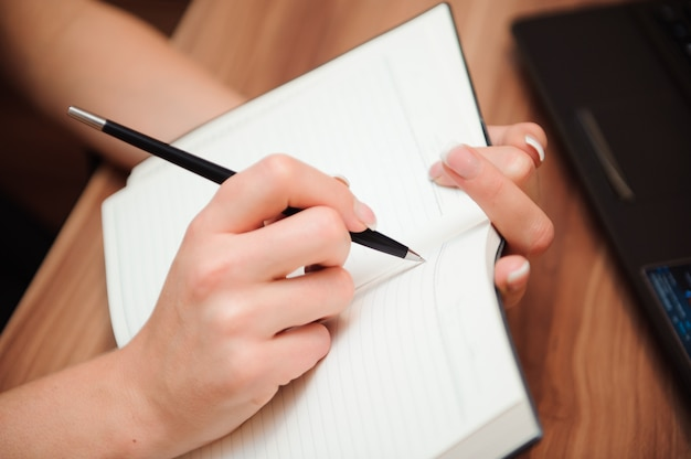 Close de uma mão feminina, escrevendo em um caderno em branco com uma caneta