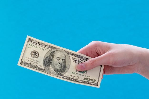 Close de uma mão feminina segurando uma nota de 100 dólares, banco de ideia de negócio