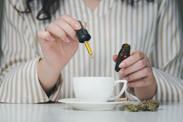 Close de uma mão feminina segurando uma pipeta com óleo cbd, pingando em canecas de café