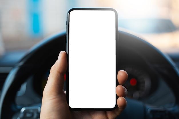Close de uma mão masculina segurando um smartphone com uma maquete branca na tela