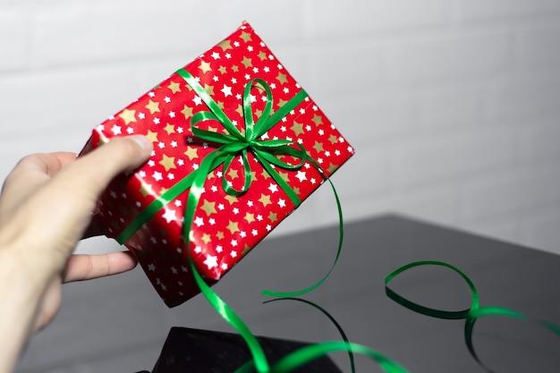 Close de uma mão masculina segurando uma caixa de presente vermelha com laço verde em vidro preto