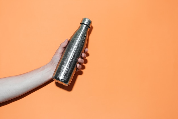 Close de uma mão masculina segurando uma garrafa térmica reutilizável de aço para qualquer líquido