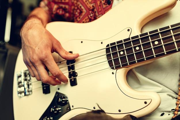 Close de uma mão masculina tocando guitarra elétrica