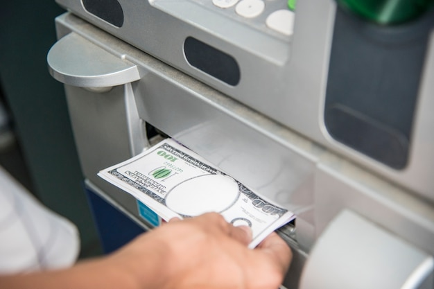 Close de uma mão recebendo dinheiro de um caixa eletrônico