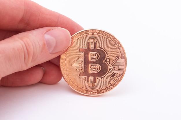 Close de uma mão segurando um bitcoin dcoin em um fundo branco Foto Premium