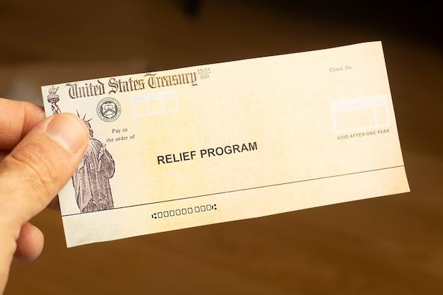 Close de uma mão segurando um cheque do programa de ajuda humanitária dos eua