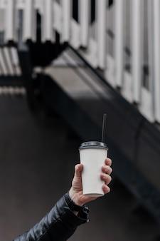 Close de uma mão segurando um copo de papel com cappuccino