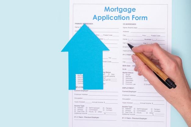Close de uma mão segurando uma caneta sobre um contrato de pedido de hipoteca de casa com uma casa azul de papel em um documento, vista superior