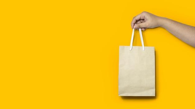 Close de uma mão segurando uma sacola de papel de compras, usando uma sacola de papel em vez de uma sacola plástica para ajudar a reduzir o aquecimento global e a degradação do plástico. isolado em um fundo amarelo e traçado de recorte.