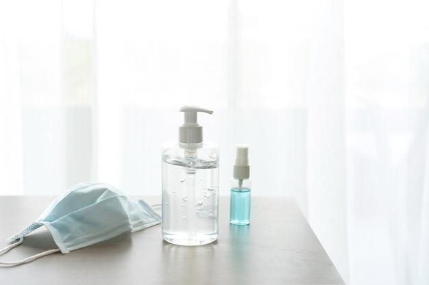 Close de uma máscara protetora, gel desinfetante e álcool em spray na mesa