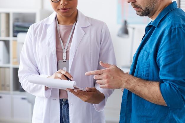 Close de uma médica apontando para o cartão médico nas mãos e mostrando algo para a paciente