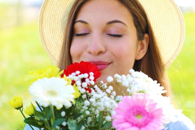 Close de uma menina bonita cheira e aprecia o perfume de um buquê de flores que acabou de receber