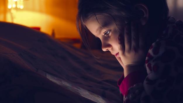 Close de uma menina bonita em plena escuridão assistindo tablet