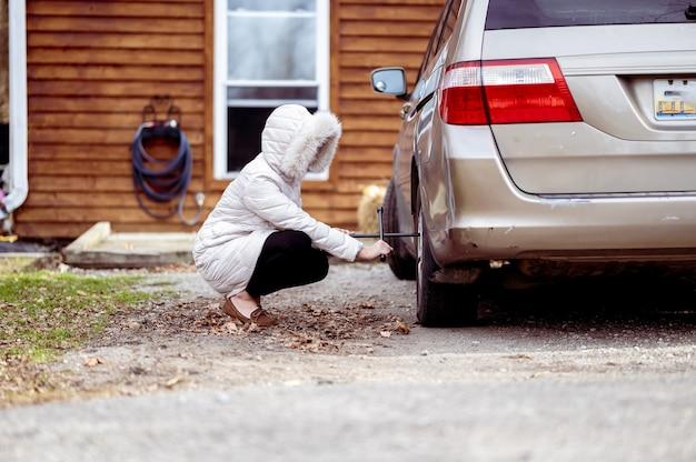 Close de uma menina consertando uma roda de carro