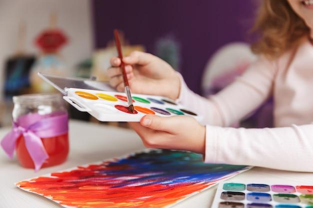 Close de uma menina pintando um quadro na mesa em casa