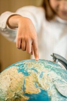 Close de uma menina segurando o dedo indicador no globo terrestre
