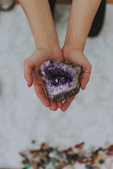 Close de uma menina segurando uma pedra multicolorida nas mãos sobre uma superfície branca