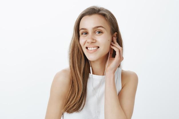 Close de uma menina sorridente colocando fones de ouvido, ouvindo música ou podcast no caminho