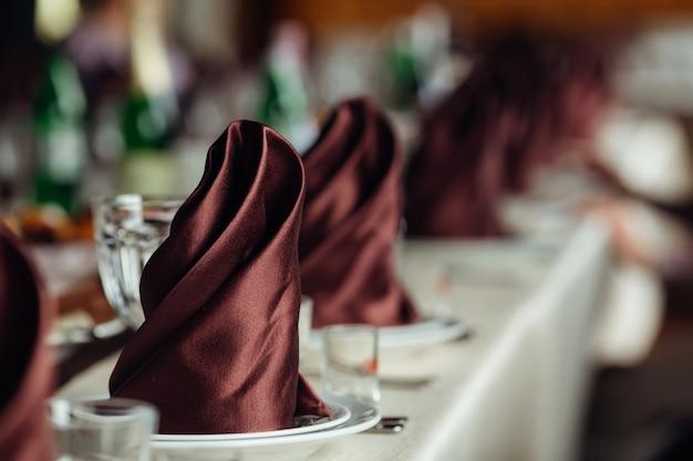 Close de uma mesa de casamento com lindos guardanapos marrons