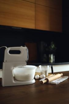 Close de uma mesa em uma cozinha caseira com uma batedeira e produtos para sobremesas. preparando-se para a preparação de alimentos.