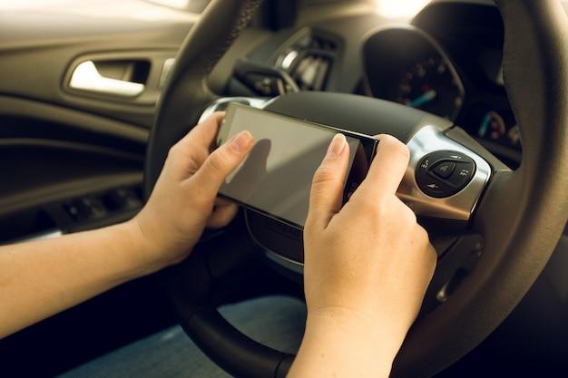 Close de uma motorista usando smartphone enquanto dirige o carro