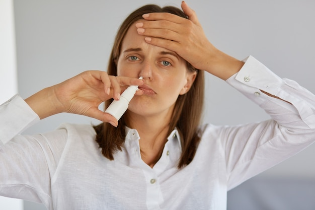 Close de uma mulher adulta jovem doente usando spray nasal, sofrendo de coriza e terrível dor de cabeça, olhando para a câmera, tocando sua testa, tendo gripe e temperatura alta.