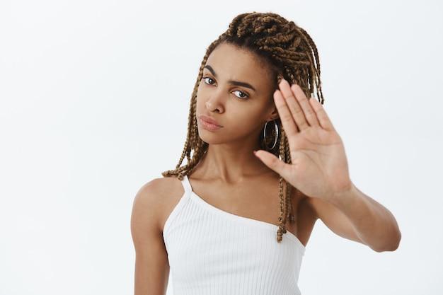 Close de uma mulher afro-americana descontente e irritada mostrando gesto de parada