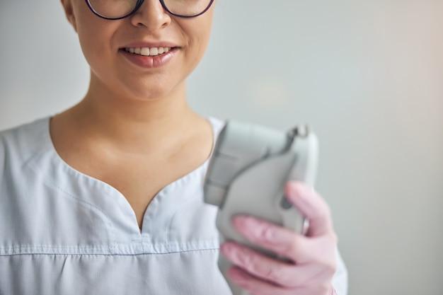 Close de uma mulher alegre esteticista em luvas estéreis segurando um dispositivo de depilação a laser e rejuvenescimento da pele